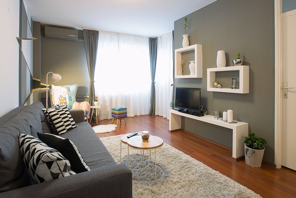 Living room with double sofa bed, tv, shelf with books and small decorations.