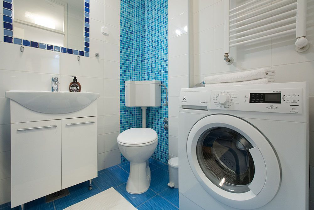 Bathroom with bath tub and shower, sink, toilet, and washing machine.