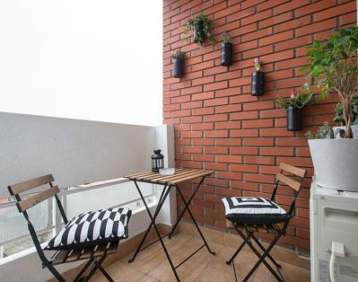 Terrace with table and chairs and flowers on the red brick wall.
