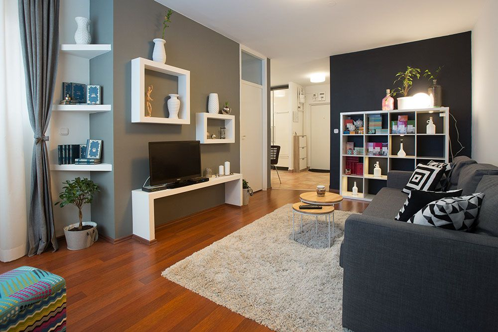 Living room with double sofa bed, armchair and shelf with books and decoration.