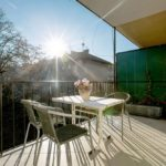 Sunny terrace with flowers and table with 4 chairs.