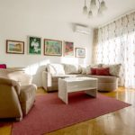 Living room with double sofa bed, armchair and exit to the sunny terrace.