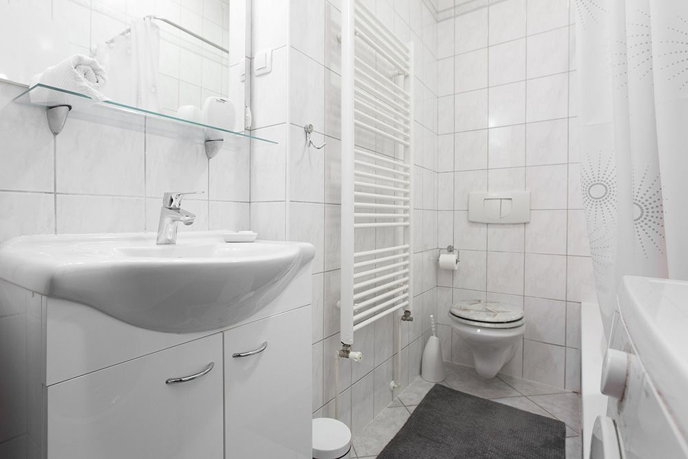 Bathroom with bath tub, toilet sink and washing machine.