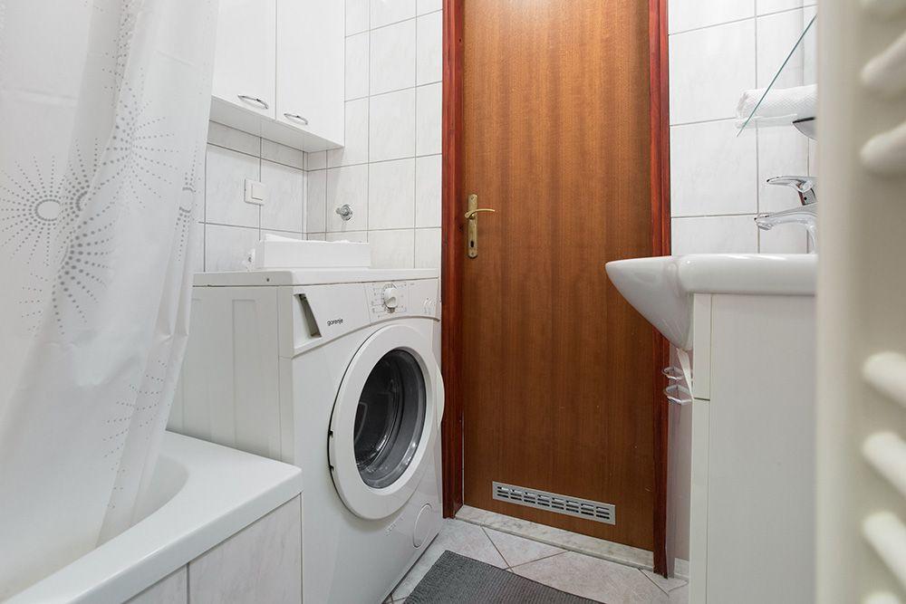 Bathroom with bath tub, toilet sink and washing machine.