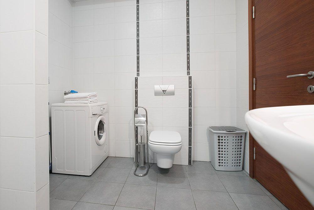 Big bathroom with shower toilet, sink and washing machine.