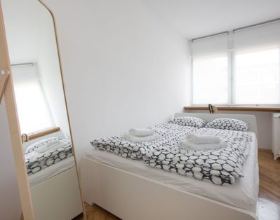 Bedroom with double bed, working table and big mirror.